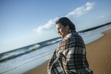 Young woman with blanket on the beach looking at the se - KIJF01312