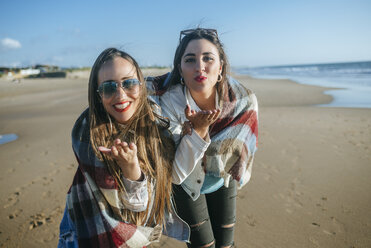 Portrait of two young women on the beach blowing kisses - KIJF01315