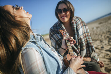 Woman playing ukulele while her friend watching her - KIJF01318