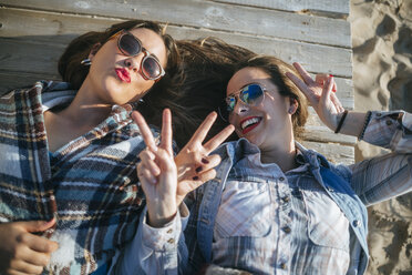 Two young women lying on wooden boardwalk showing victory signs - KIJF01321