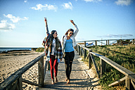 Two happy young woman walking barefoot on boardwalk - KIJF01324