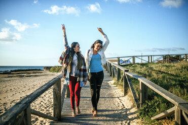 Two happy young woman walking barefoot on boardwalk - KIJF01324