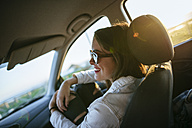 Young woman with sunglasses in car at evening twilight - KIJF01330
