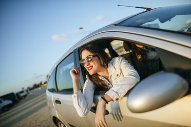 Young woman leaning out of car window - KIJF01333