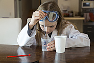 Girl wearing work coat and safety glasses using chemistry set at home - SARF03222
