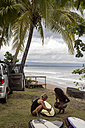 Indonesia, Java, two women preparing surfboard at the coast - KNTF00650