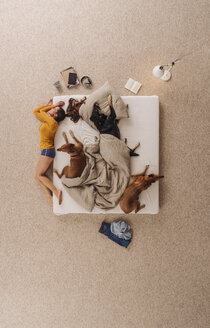 Woman sleeping in bed with her dogs, lying on the edge - JOSF00655