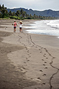 Indonesia, Java, back view of two women walking on the beach - KNTF00657