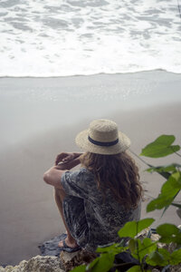 Indonesia, Java, woman wearing straw hat sitting on rock on the beach looking to the sea - KNTF00660