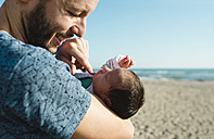 Father with his newborn baby girl on the beach - GEMF01521