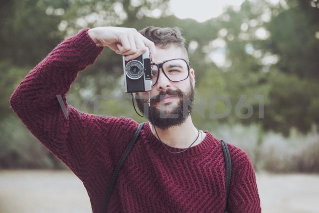 Portrait of bearded man with glasses taking photo with vintage camera - RTBF00720