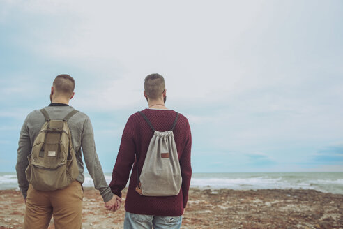 Back view of young gay couple with backpacks standing hand in hand on the beach looking at the sea - RTBF00723