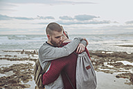 Young gay couple with backpacks hugging on the beach - RTBF00729