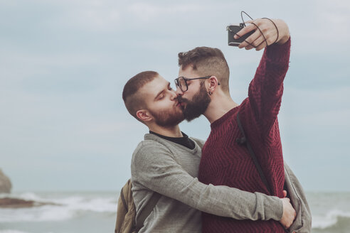 Gay couple taking selfie while kissing in front of the sea - RTBF00735