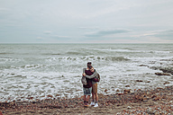 Gay couple hugging on the beach in front of the sea - RTBF00738