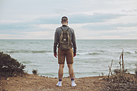 Back view of young man with backpack looking to the sea - RTBF00744