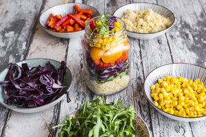 Glass of rainbow salad with bulgur, rocket and different vegetables and bowls with ingredients - SARF03241
