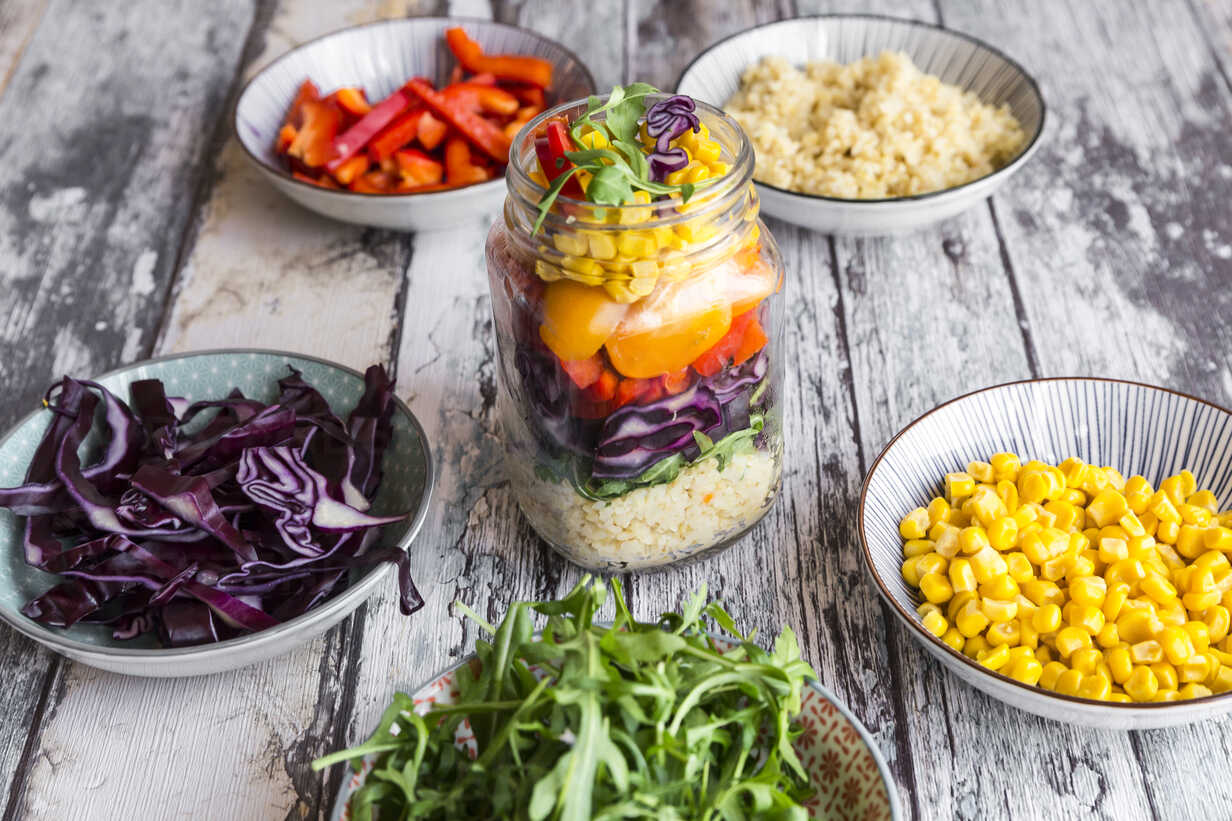 Glass of rainbow salad with bulgur, rocket and different vegetables and bowls with ingredients - SARF03241 - Sandra Roesch/Westend61