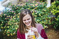 Young woman in Sevilla drinking fruit juice - KIJF01337
