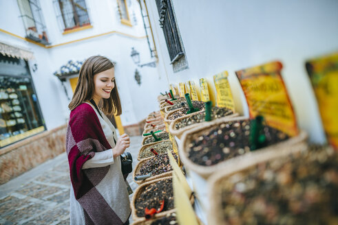 Young woman in Sevilla looking at spice shop - KIJF01343