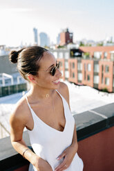 Relaxed woman standing on rooftop in Brooklyn - GIOF02098