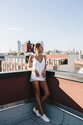 Relaxed woman standing on rooftop in Brooklyn - GIOF02101