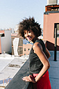Relaxed woman standing on rooftop in Brooklyn - GIOF02104