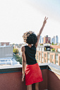 Happy young woman standing on rooftop in Brookly making victory sign - GIOF02110