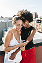 Female friends standing on rooftop, embracing and holding smart phones - GIOF02113