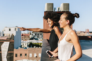 Female friends standing on rooftop, pointing at distance - GIOF02116