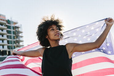 Young woman standing on rooftop holding US American flag - GIOF02119