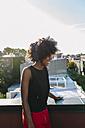 Laughing young woman on rooftop iin Brookly wearing headphones - GIOF02122