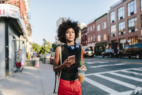 Young woman with headphones and smart phone crossong street in Brooklyn, carying take away drink - GIOF02128