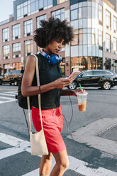 Young woman with headphones and smart phone crossong street in Brooklyn, carying take away drink - GIOF02131