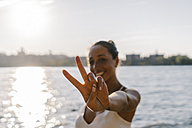 Young woman in Brooklyn standing at East River giving victory sign - GIOF02134