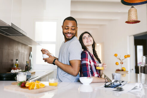 Young couple having breakfast in the kitchen, standing back to back - VABF01204