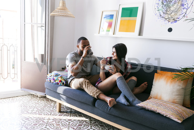 Young couple sitting on sofa, eating breakfast - VABF01210 - Valentina Barreto/Westend61