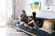 Young couple sitting on sofa, eating breakfast - VABF01210