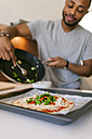 Young couple baking pizza at home - VABF01219