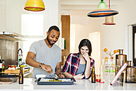 Young couple baking pizza at home - VABF01231