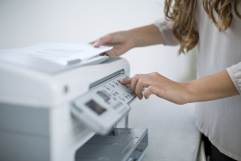 Office worker pressing button of a printetr - ZEF13106