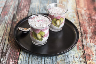 Two glasses of chia pudding with heart-shaped kiwi slices on tray - SARF03247