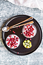 Two glasses of chia pudding with kiwi  and pomegranate seed on tray - SARF03250