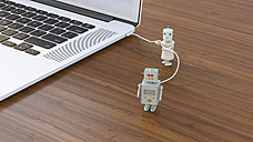 Male robot being charged at laptop, 3D rendering - UWF01140