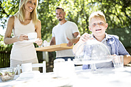 Smiling boy with his parents laying garden table - WESTF22770