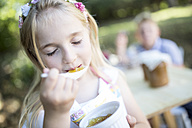 Girl eating jelly outdoors - WESTF22785