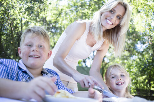 Smiling mother with children at garden table - WESTF22788