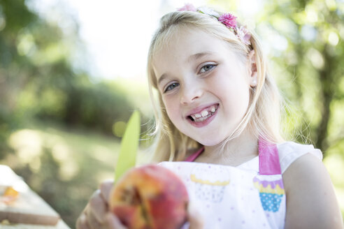 Portrait of smiling girl outdoors holding peach - WESTF22803