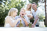 Portrait of boy with family eating gherkin outdoors - WESTF22815