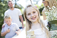 Portrait of smiling girl outdoors with family in background - WESTF22818
